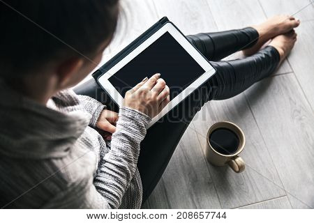 the girl is sitting in a tablet and with a cup of coffee in a warm sweater on the floor