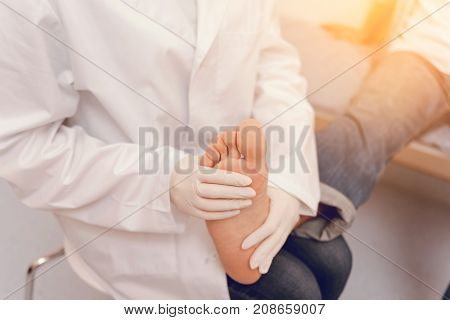 Put it here. Competent medical worker wearing white smock and having rubber gloves on hands while sitting at her workplace