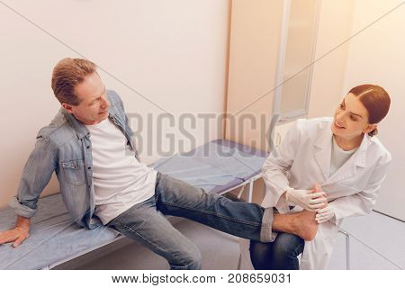 You are health. Concentrated man leaning hands on couch and sitting near his doctor while putting leg on knees of his practitioner
