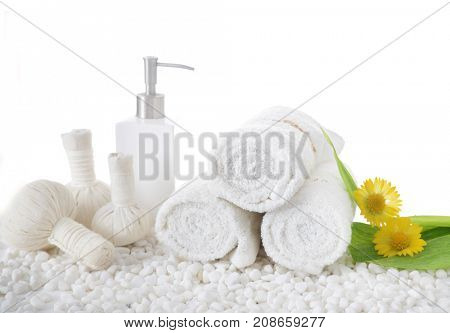 Yellow flower on three rolled towel ,bottle oil with herbal ball.leaf on pile of white stones