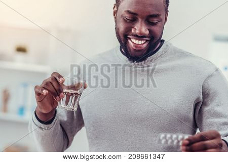 Such a relief. Beaming millennial guy in casual looking a blister with pills while holding a glass of water and taking his prescription.