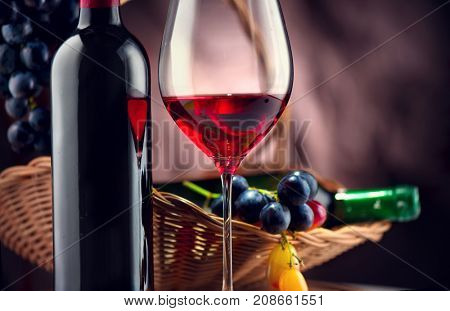 Wine. Bottle and glass of Red wine with ripe grapes still life. Red wine Over black background. Art design