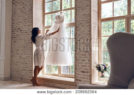 Looks just right. Full length of beautiful young woman in silk bathrobe touching her wedding dress while standing near the window