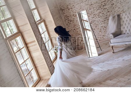 Dancing queen. Top view of young woman in silk bathrobe trying on her wedding dress while standing near window