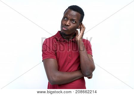 young black man with thoughtful expression scratching his head in thought and posing for portrait on white background in red shirt