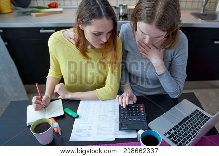 two Caucasian women Housewives girlfriends sitting at the kitchen table with a stack of papers bills notices from banks a laptop and a calculator and count forecast home budget taxes the loan.