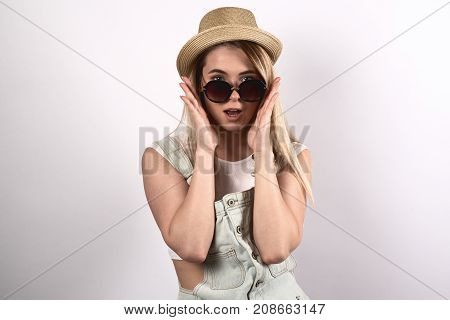 stylish young attractive woman does not believe his eyes. A surprised shocked expression dreamy. Sunglasses and hat hands are at the cheeks portrait on white background.