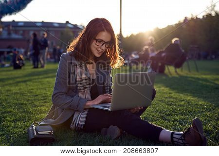 young female student doing homework on laptop sitting on green grass in the Park. Red long hair and glasses. Concept training business communication outside the building