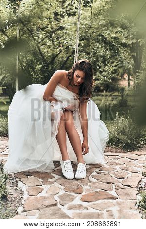 Beautiful modern bride. Attractive young woman in wedding dress adjusting her sports shoes while sitting on the swing outdoors