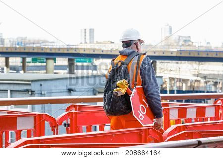 Back View Of A Construction Worker With A Stop Waning Sign In A Building Site In Canary Wharf