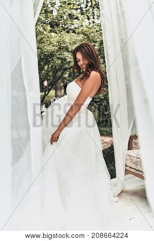 Happiest bride. Full length of attractive young woman in wedding dress smiling while standing outdoors
