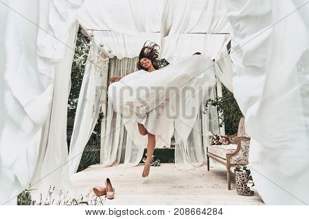 Bride in the mid air. Full length of attractive young woman in wedding dress smiling while jumping in the wedding pavilion outdoors