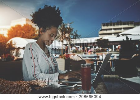 Beautiful young black female entrepreneur is sitting in street bar and working remotely on her project with laptop; charming African American freelancer girl is sitting in cafe outdoor with netbook