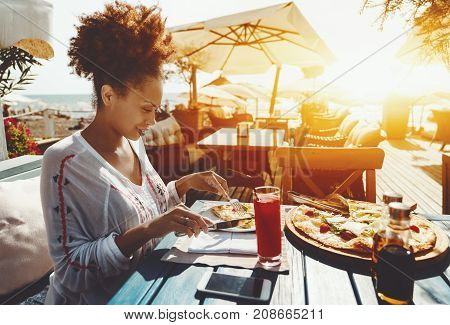 Attractive young black female using knife and spork to cut hot piece of delicious freshly baked pizza with cheese cherry tomatoes and salad while sitting in luxury restaurant outdoor warm sunny day