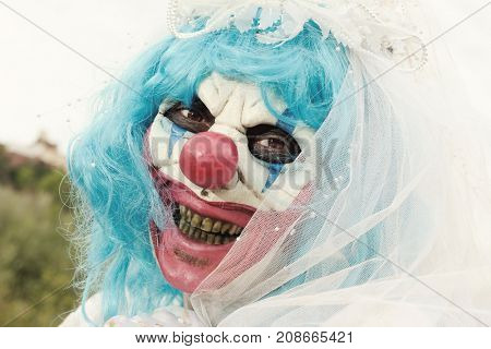 closeup of a scary evil clown outdoors wearing a bride dress, with a veil and a diadem