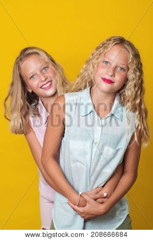 Twins Teenager Girls Having Fun Together, Isolated On A Yellow Background.