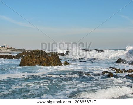 WINTER SEASCAPE, WITH ROUGH SEAS, AND WHITE WAVES SMASHING OVER SOME BOULDERS 07sds
