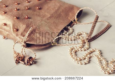 The open women's pink evening handbag or clutch embroidered with pearls and pearl necklace on the grey concrete background. Stylish women's accessories. Fashion set. Selective focus