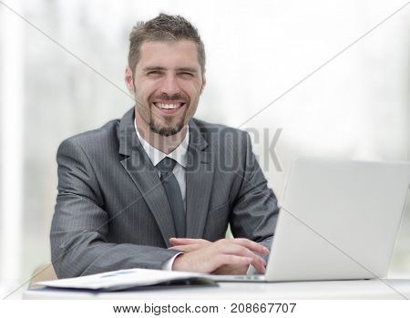 closeup.smiling businessman working with laptop