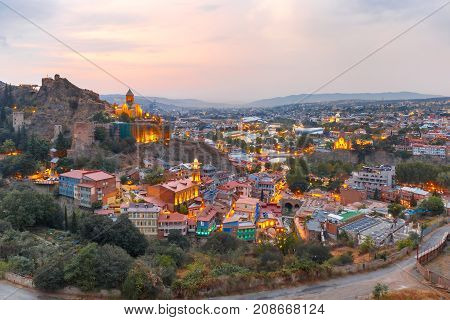 Amazing panoramic view of Narikala ancient fortress and Sameba Holy Trinity Cathedral, Metekhi Church, bridge of Peace and Presidential Palace in old historic district Abanotubani in night Illumination at sunset, Tbilisi, Georgia.