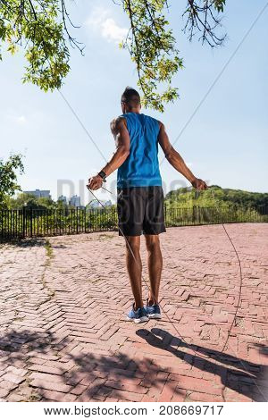 rear view of athletic sportsman jumping on skipping rope in park