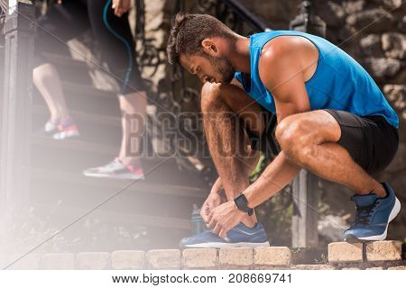 young athletic sportsman tying shoelaces on sneakers