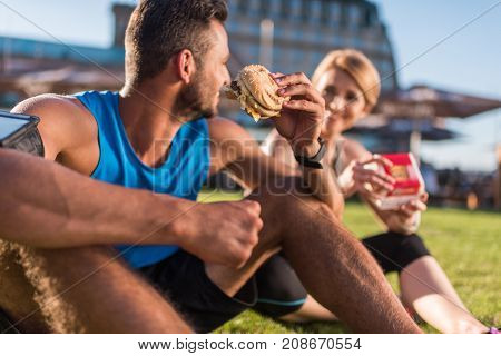 athletic sportswoman and sportsman eating junk food