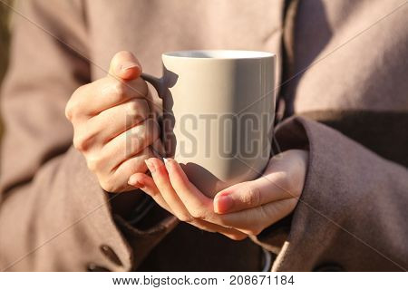 Closeup View Of Disposable Cup Of Coffee Or Tea In Womans Hand. Autumn Park With Trees And Yellow Le