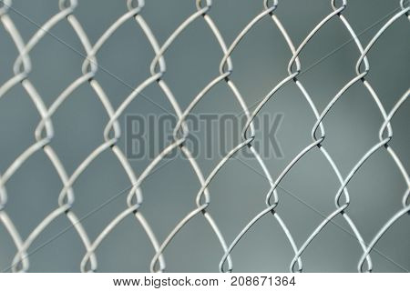Silvery Fence Made Of Metal Mesh Of The Slab, On A Gray Fuzzy Background. Close-up