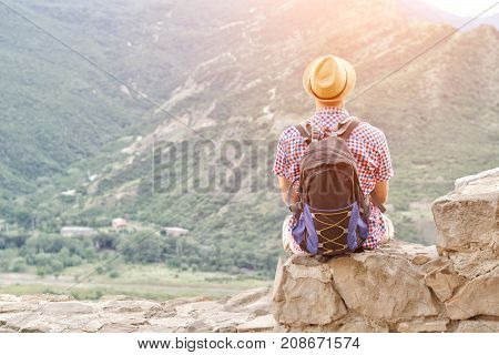 Young Man In A Hat With A Backpack Sits On A Stone Wall Against A Background Of Green Mountains. Bac