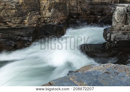 Soft rapids in a river, surrounded of cliffs, rocks. Some sunshine.