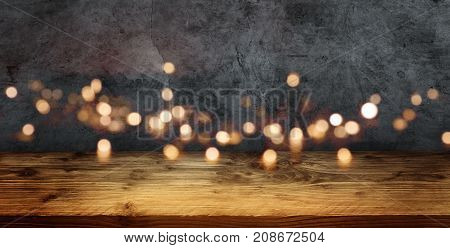 Gray old concrete wall with golden bokeh and rustic wooden table for a presentation
