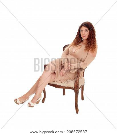 A lovely young woman in a beige dress relaxing in an old armchair with big boobs and curly brunette hair isolated for white background