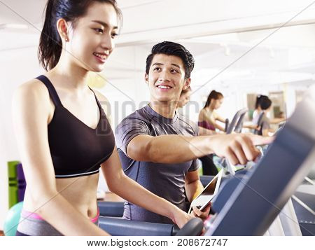 young asian woman running on treadmill coached by young trainer.