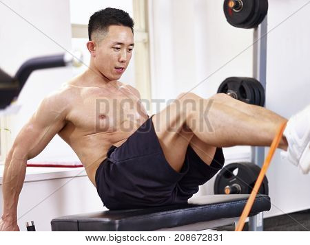 asian male bodybuilder exercising in gym with a resistance band.