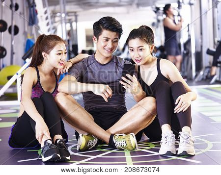 young asian man and women using mobile phone in gym while taking a break during exercising.
