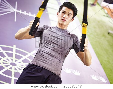 young asian man exercising in gym using fitness straps.