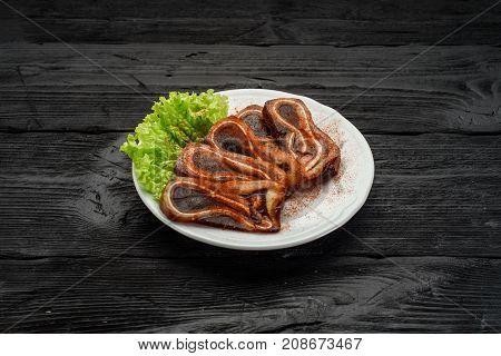 Grilled Pork Ears On A White Plate Over Dark Rustic Background. Beer Snack.