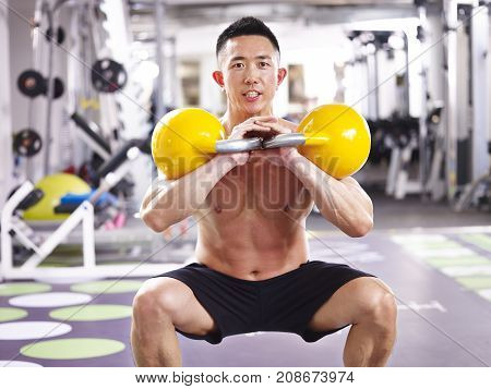 asian male bodybuilder working out in gym using kettle bells.