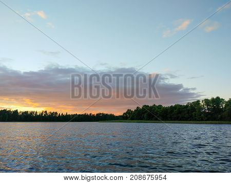Calm lake surface at evening. Summer sunset landscape with water and forest.