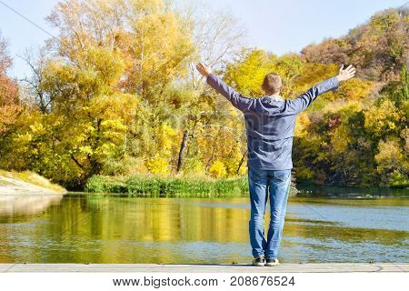Man With Arms Raised Standing On The Dock. Autumn, Sunny. Back View