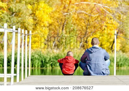 Father And Son Are Sitting On The Dock. Autumn, Sunny. Back View