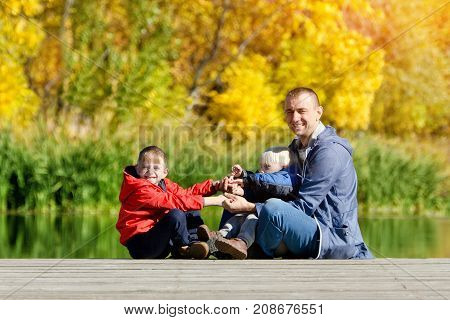 Father And Two Sons Play On The Dock. Autumn, Sunny. Side View