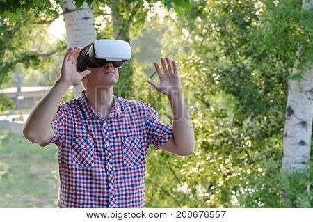 Man In A Helmet Of Virtual Reality Against The Background Of Nature.hands Up