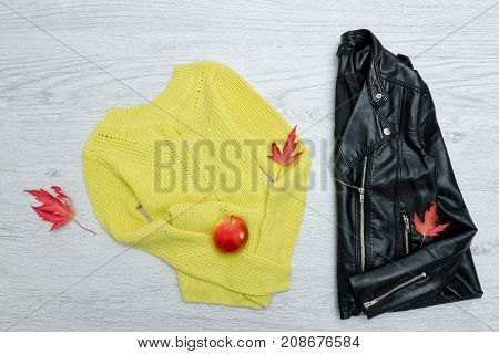 Bright Sweater, A Black Jacket, A Red Apple And Leaves. Fashionable Concept.