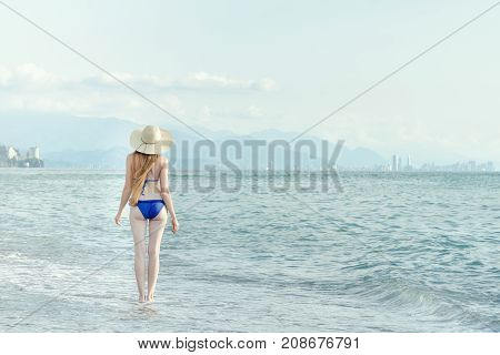 Girl In A Bathing Suit And Hat Walks By Sea. View From The Back
