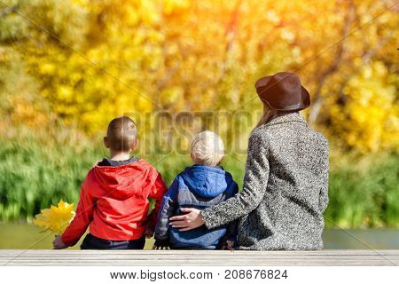Mom And Two Children Are Sitting On The Pier. Sunny Autumn. Back View