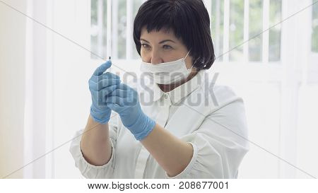 Middle-aged woman cosmetician in special suit and gloves looks at syringe with medicine to measure the right dose