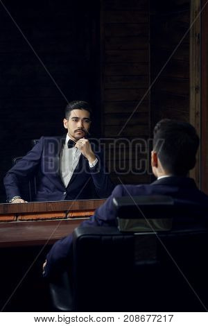 Serious Man In Blue Suit And Butterfly Sitting In Chair Looking In The Mirror In Barbershop