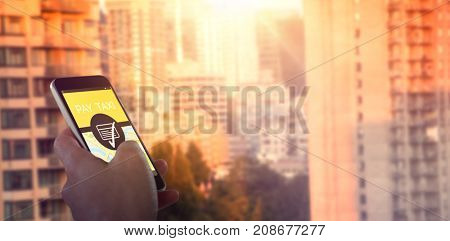 Close-up of hand holding mobile phone against sunlight falling on buildings